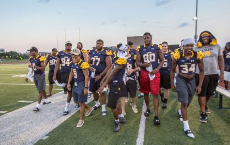 The Lion Football team marches onto the field.