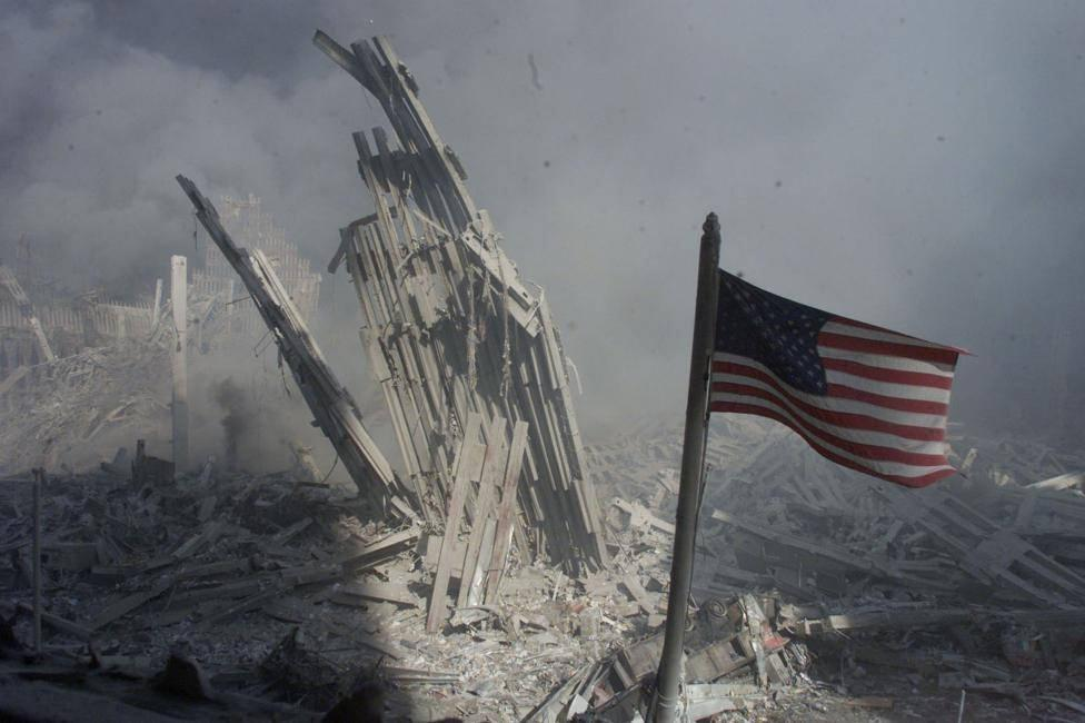 An American flag flies over the rubble of the Twin Towers.