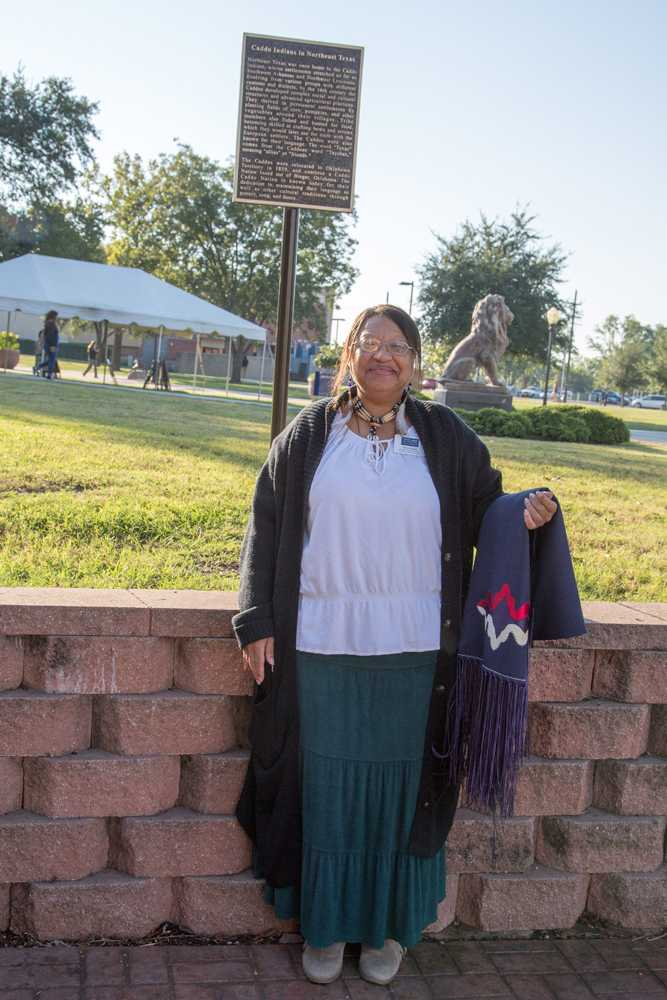 Terryl Bratek stands in front of a plaque commemorating the Caddo Indians that once settled this area.