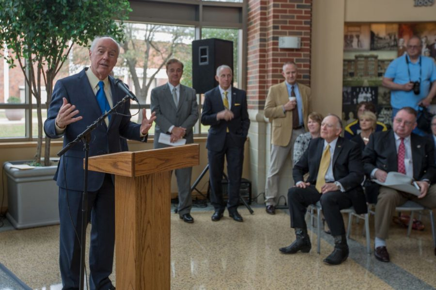 President Ray Keck addresses the crowd during the groundbreaking with Chancellor Sharp (standing first to the left of Keck) and State Rep. Flynn (sitting second from the right) nearby.