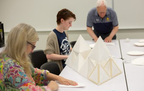 The Paper Plate Sculpture Workshop, led by Wyman Williams (back), had participants fold paper plates to form different shapes or to combine these shapes into a sculpture.