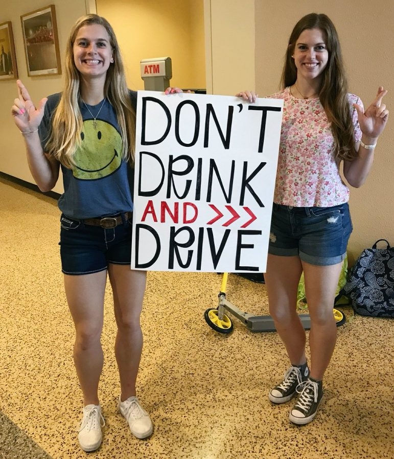 Volleyball twins Jaryn (left) and Jaryn (right) Wacker hold up a sign during a Responsible Lions campaign during Homecoming. Courtesy | Jaslyn Wacker Twitter