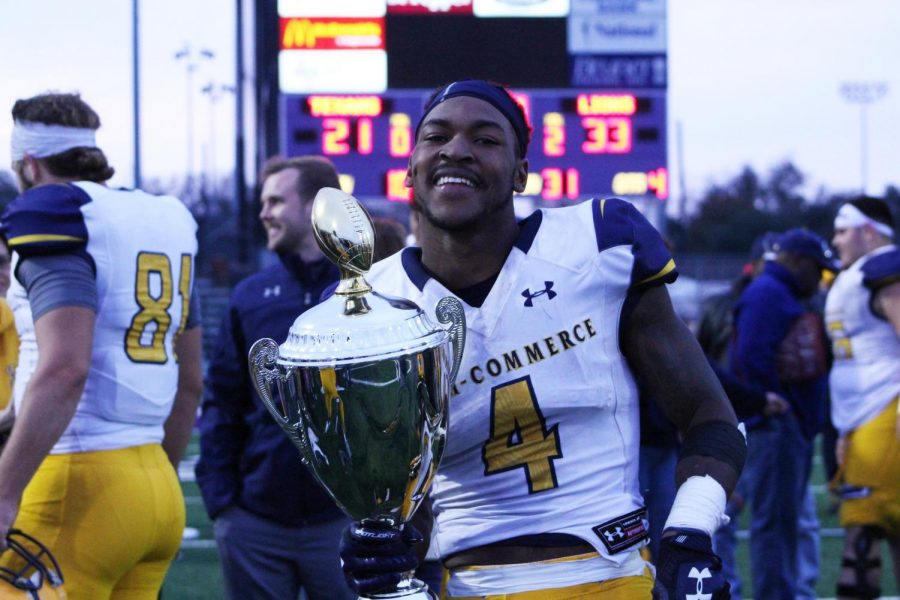 Lion wide receiver Buck Wilson, who had 193 receiving yards with one touchdown, holds aloft the Presidents Cup trophy.