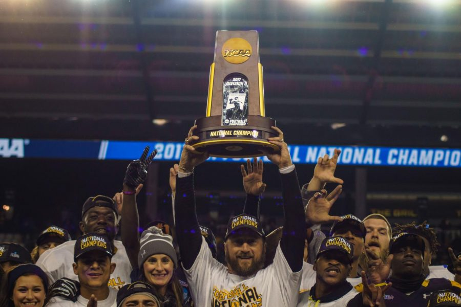 As the stadium lights shine down, Lions head coach Colby Carthel holds the championship trophy high above his head in celebration with his players. Carthel has brought the football program from consecutive 1-9 seasons before his arrival to three consecutive conference championships and, seen here, a national championship.