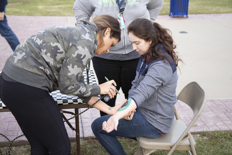 Airbrush+tattoo+artist+Kayla+Simpson+gives+Kaylyn+Costilla%2C+junior+a+temporary+tattoo.+East+Texan+Photo+%7C+John+Parsons
