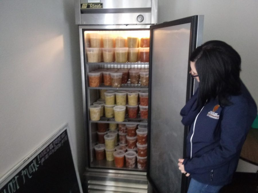 Nikki Barnett opens the freezer unit that was donated to the pantry by Sodexo last semester.