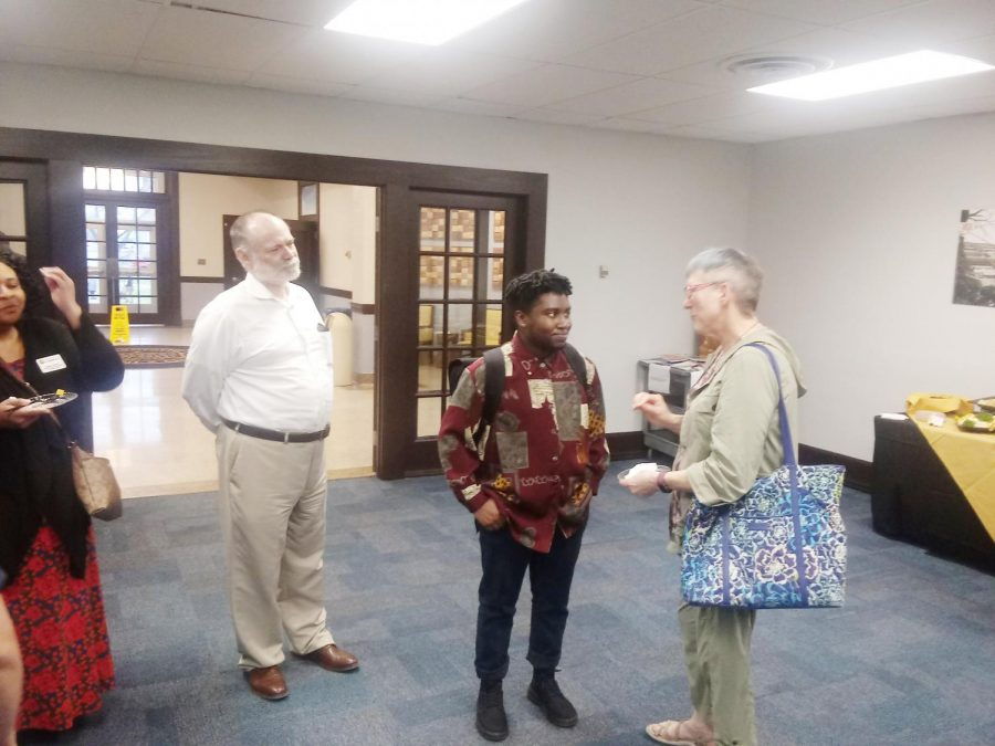 Kavi Ade (middle) talks to Dr. Robin Reid (right), Literature and Languages professor.