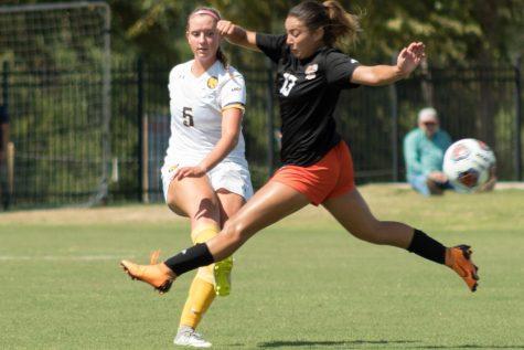 Katie Loken kicks the ball past an outstretched Lauren Marenco