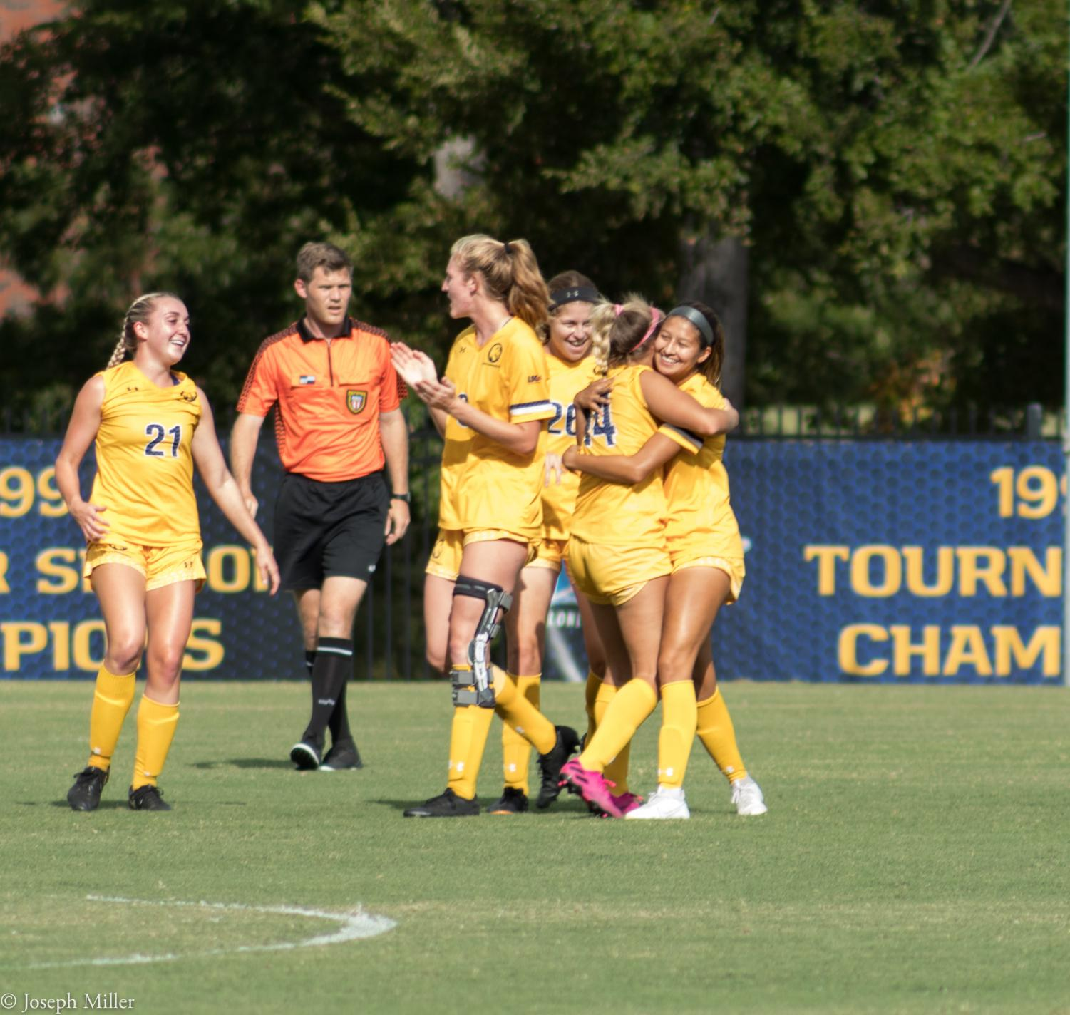 The Lions celebrate with Leslie Campuzano after her goal