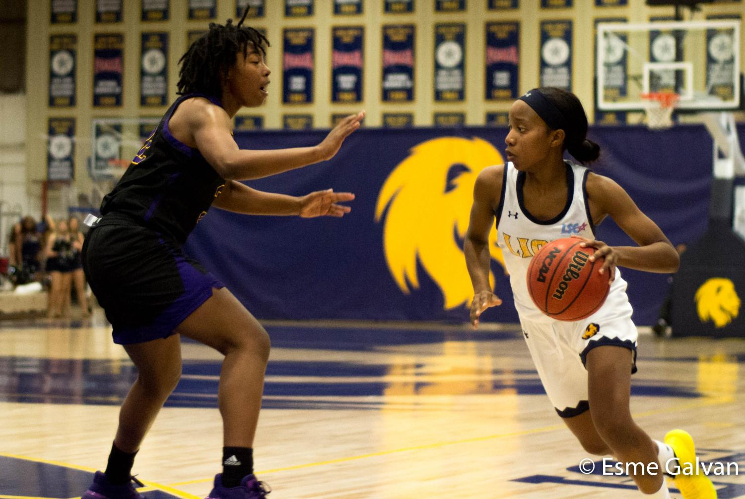 Chania Wright (right) dribbles past Jakyya Clay of the Ouachita Baptist Tigers