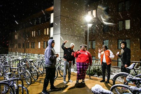 Residents smile next to the snow covered bicycles behind Phase III.
